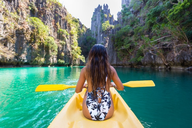 Woman kayaking in the small lagoon in el nido, palawan, philippines - travel blogger exploring south-east asia best places
