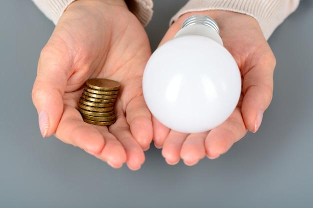 여자는 당신의 동전과 led 전구를 유지