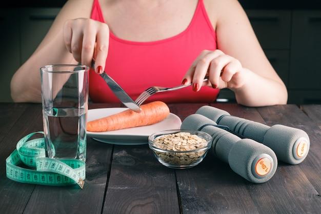 다이어트를 유지하고 부엌에서 당근을 먹는 여자