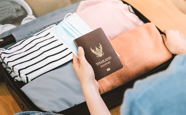 Woman keeping clothes and holding passport with mask in luggage.