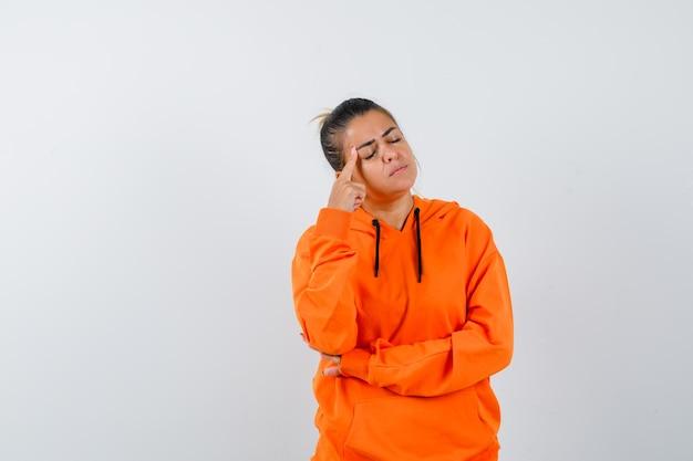 Donna che tiene il dito sulle tempie in felpa con cappuccio arancione e sembra pensierosa