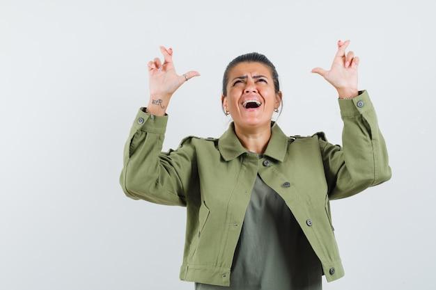 여자 재킷, 티셔츠에 손가락을 유지하고 행복을 찾고