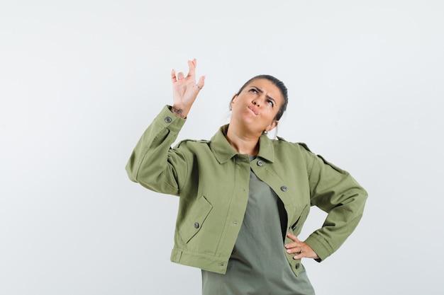 Donna tenendo le dita incrociate in giacca, t-shirt e guardando pensieroso