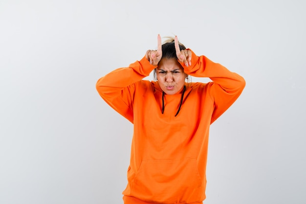 Woman keeping fingers over head as bull horns in orange hoodie and looking funny