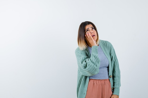 カジュアルな服装で頬に手を当てて困っている女性、正面図。