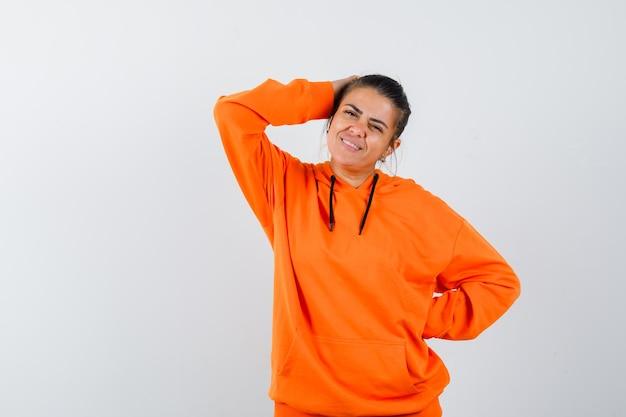 주황색 후드티를 입고 머리에 손을 얹고 매력적으로 보이는 여성