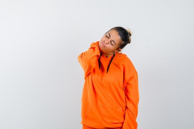 オレンジ色のパーカーで首に手を保ち、疲れているように見える女性