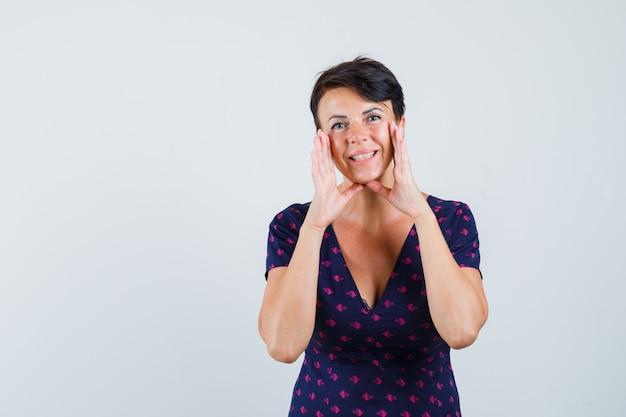 Donna che mantiene le mani per raccontare il segreto in abito e che sembra felice
