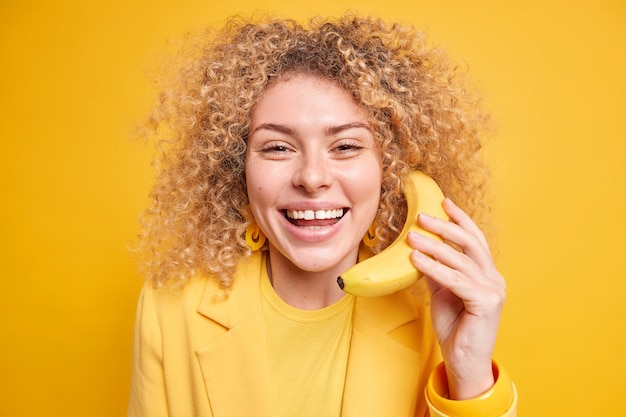 Женщина держит банан возле уха широко улыбается, веселится, одетая в элегантную одежду, имеет счастливое выражение