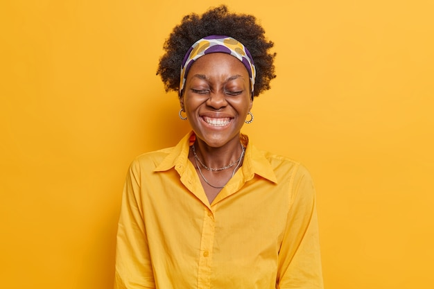 Woman keeps eyes closed laughs happily chuckles carefree shows white teeth wears headband and shirt isolated on vivid yellow
