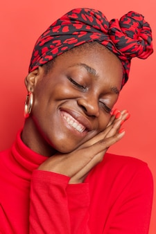 Woman keeps eyes closed tilts head hands pressed together near face has gentle expression wears silk scarf tied on head casual turtleneck isolated on red