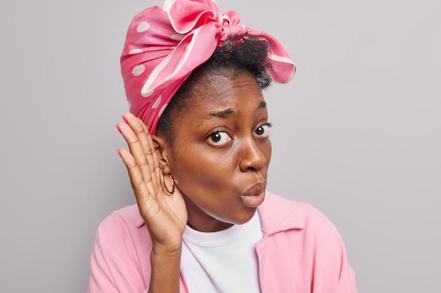 여자는 귀에 손을 가까이 대고 소문을 들으려 하고 흥미로운 표정을 하고 회색 벽에 격리된 머리에 묶인 분홍색 재킷 스카프를 착용하고 대화를 들으려 합니다