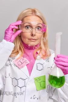 여자는 투명한 안경에 손을 얹고 녹색 액체 김이 나는 튜브를 들고 회색으로 격리된 흰색 코트를 입고 놀란 표정을 하고 있다
