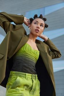 여자는 세련된 녹색 재킷과 청바지를 입은 머리 뒤로 손을 유지하고 친구들과 시간을 보낼 준비가 된 회색 배경에 밝은 메이크업 포즈를 취합니다