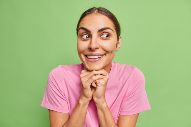 Woman keeps hands under chin smiles happily looks with curious expression aside wears casual pink t shirt on green notices something interesting