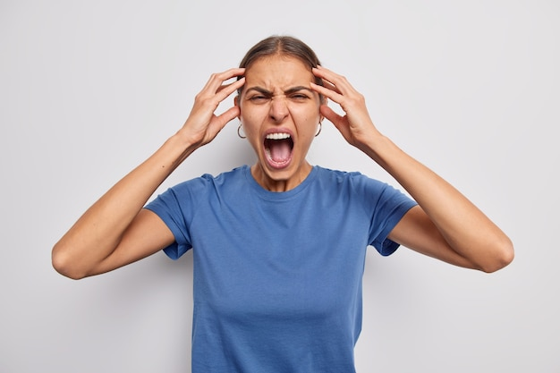 Woman keeps hands on head yells angrily keeps mouth wide opened loses control has mental breakdown screams furious wears blue t shirt on white relieves from stress