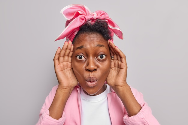 La donna tiene le mani vicino al viso fissa incredula sembra stupita indossa un fazzoletto giacca rosa mantiene le labbra arrotondate isolate su grigio
