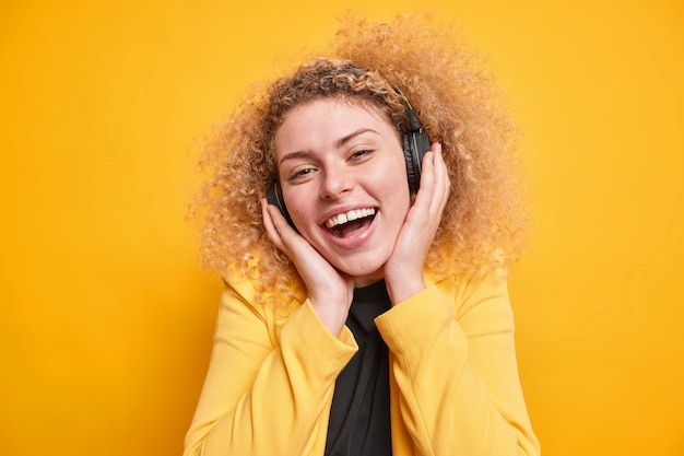 Woman keeps hands on stereo wireless headphones smiles broadly being in good mood dressed in formal jacket enjoys spare time