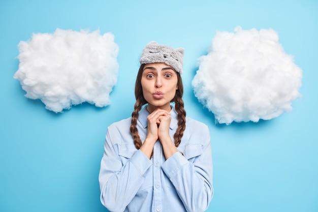 여자는 턱 아래에 손을 유지하고 파란색에 고립 된 건강한 수면 후 눈가리개를 착용하고 캐주얼 셔츠를 입는다.