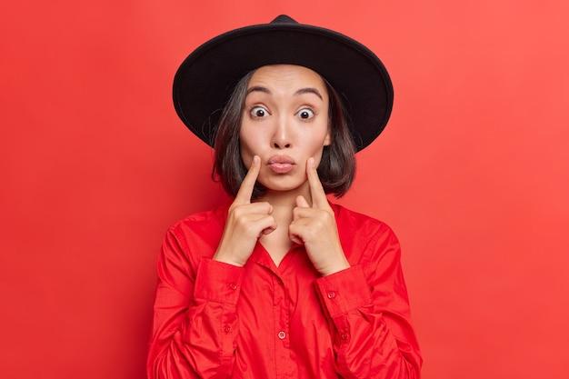 女性は頬に人差し指を保ちます折りたたまれた唇はスタイリッシュな服を着た誰かにキスしたい鮮やかな赤で健康的なきれいな肌のポーズを持っています