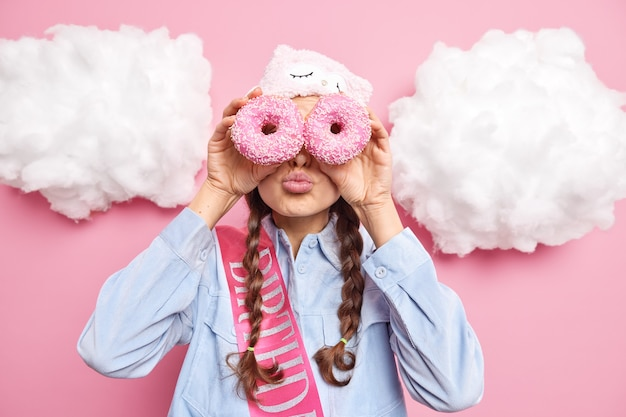 La donna tiene le labbra piegate contro gli occhi con gustose deliziose ciambelle vestite con abiti casual posa contro il rosa