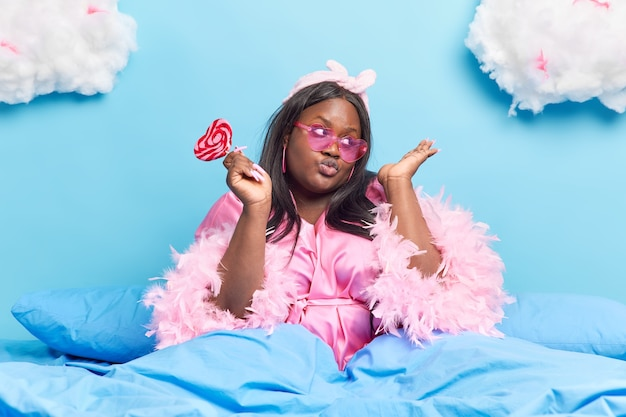 Woman keeps lips folded dressed in stylish domestic clothes wears trendy sunglasses holds delicious candy poses on comfortable bed on blue Free Photo