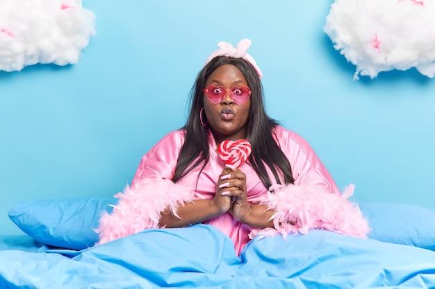 여자 입술 접힌 유지 맛있는 달콤한 롤리팝은 심장 모양의 선글라스를 착용하고 따뜻한 담요 아래 편안한 침대에 드레싱 가운 포즈는 게으른 하루가 있습니다