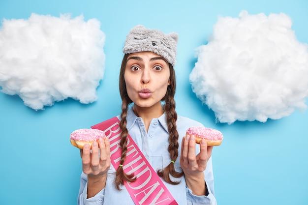 Женщина держит губы сложенными держит два вкусных пончика имеет искушение съесть сладкий десерт, носит рубашку с маской для сна и день рождения ленты позирует на синем фоне