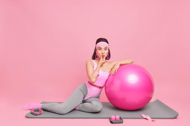 여자는 카메라에 충격을 받은 표정으로 입술을 접고 바디수트를 입은 밝은 화장을 하고 매트에서 전신 포즈를 훈련하기 위해 fitball을 사용합니다