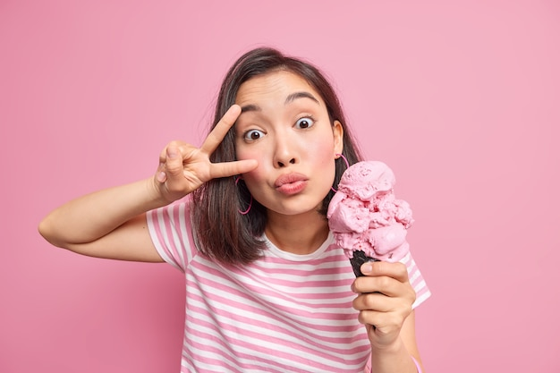 Woman keeps lips folded makes peace gesture over eye dressed in striped t shirt holds tasty ice cream for sweet tooth