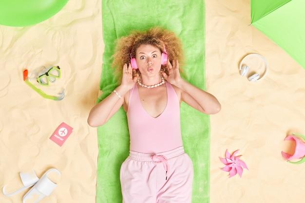여자는 입술을 접고 여름 옷을 입은 스테레오 헤드폰을 착용하고 녹색 수건에 누워 다양한 항목으로 둘러싸인 해변에서 완벽한 휴가를 즐깁니다.
