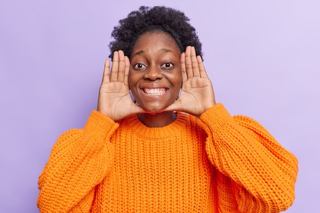 女性は手のひらを顔の近くに保ちます笑顔は広く幸せに満ちた目は愚か者の周りに紫色で分離されたオレンジ色のニットジャンパーを着ています