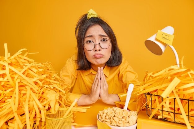 Woman keeps palms pressed together asks for favor to give her one more chance sits at desktop surrounded by cut paper piles on yellow