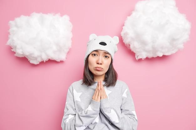 女性は手のひらを一緒に押したまま助けを求める、もう一度チャンスをくれと頼むピンクに隔離された柔らかいパジャマと帽子を着ている