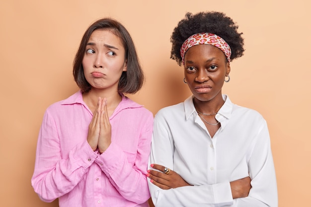Woman keeps palms pressed together in pray looks with pleading expression dressed in casual pink shirt. unhappy dark skinned keeps arms folded being offended.