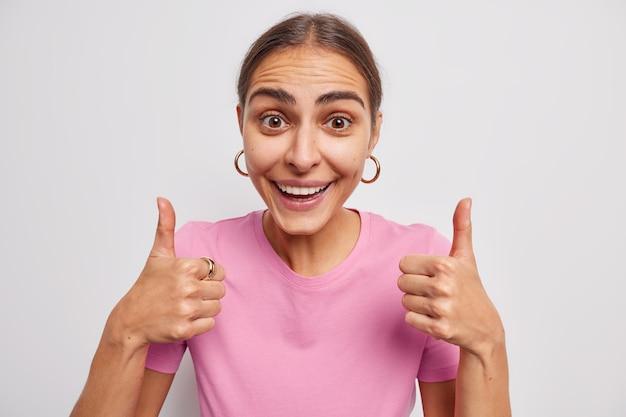 La donna tiene il pollice in alto approva o loda qualcosa consiglia il prodotto sorride felicemente vestita casualmente su bianco