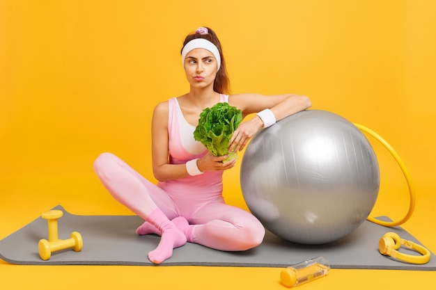 女性はダイエットを続けます健康を保つための定期的なフィットネストレーニングを持っていますスポーツ服に身を包んだ緑の野菜を保持しますヘッドフォンでマットの上に座っていますダンベルスイスボールフラフープジムで