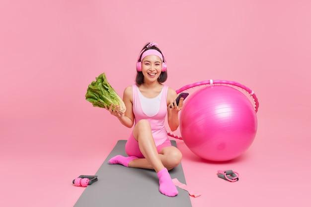 다이어트를 하는 여성은 헤드폰을 통해 음악을 듣는 피트니스 매트에서 온라인 채팅을 위해 현대적인 스마트폰을 사용하여 녹색 채소를 유지합니다.