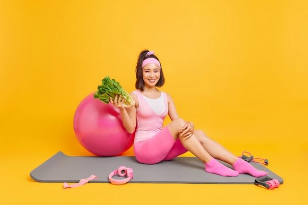 Женщина придерживается здоровой диеты держит зеленые свежие овощи сидит на коврике позирует вокруг спортивного инвентаря