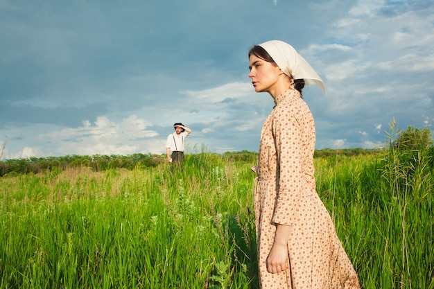 Woman in kerchief and man in hat on green meadow