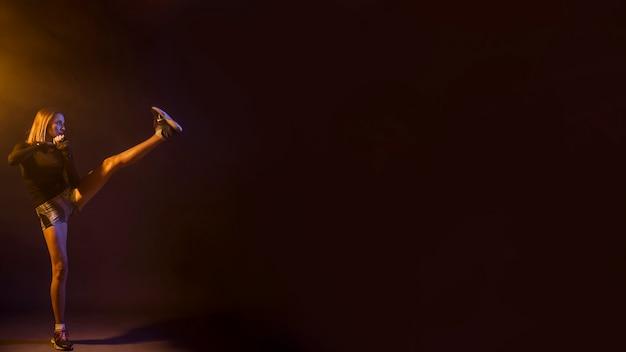 Woman kickboxing in darkness of studio
