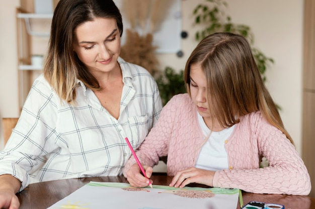 Woman and kid drawing together