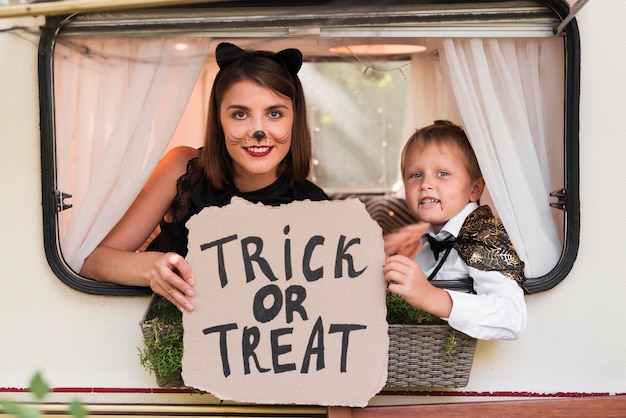 Woman and kid posing with halloween sign
