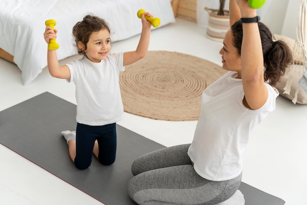 Woman and kid training with dumbbells