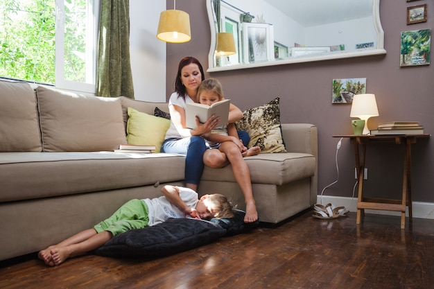 Woman and kids relaxing reading book