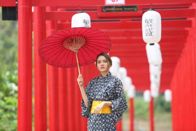 A woman in kimono holding umbrella walking into at the shrine, in japanese garden.