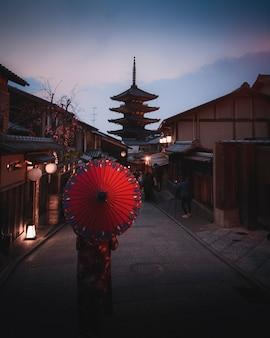 Woman in a kimono walking with a red umbrella at yasaka pagoda in kyoto, japan
