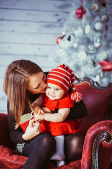 Woman kisses her daughter sitting on red leather armchair