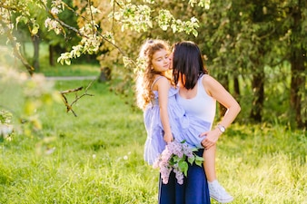 Woman kissing her daughter in park