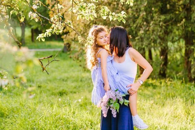 Женщина целует дочь в парке